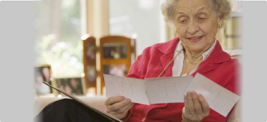 an old woman reading a letter